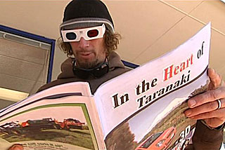 A man reads the special edition 3D paper 'Heart of Taranaki'