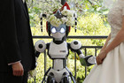 A humanoid robot named &quot;I-Fairy&quot; acts as a witness at the wedding ceremony between Tomohiro Shibata and Satoko Inoue in Tokyo (Reuters)