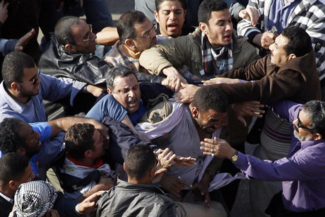 A pro-Mubarak supporter is held by anti-Mubarak demonstrators during clashes at Tahrir Square in Cairo (Reuters)