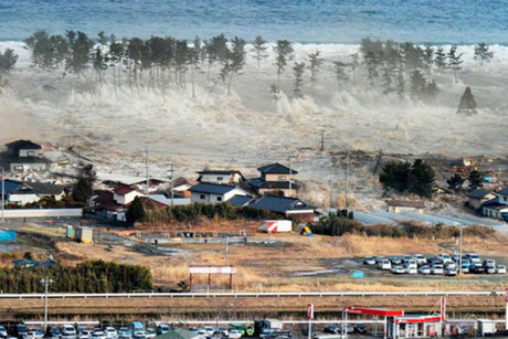 Houses are swept by water following a tsunami and earthquake near Japan