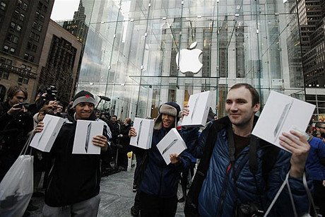 Customers hold up their Apple's iPad 2 tablets after purchasing the second generation devices at the Apple's flagship 5th Ave store in New York (Reuters)