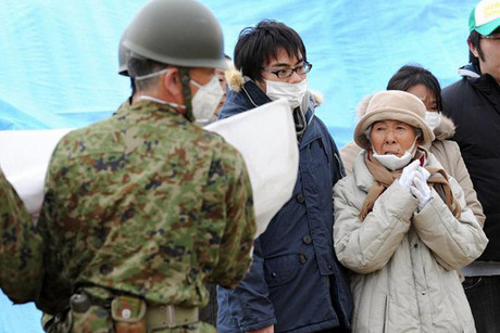 Survivors of the earthquake and tsunami watch Japan Ground Self Defense Force members bury victims in Higashi Matsushima (Reuters)