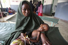 A woman holds her malnourished child on arrival at Banadir hospital in Mogadishu (Reuters)