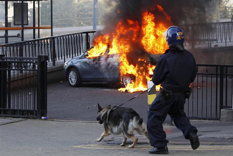 A policeman and his dog walk towards a burning car in central Birmingham, central England (Reuters)