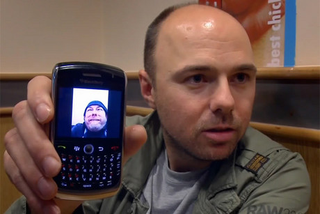Karl Pilkington holding his phone, which is displaying a self-portrait of Ricky Gervais