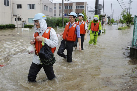 Residents walk in a flooded street to evacuate in Nagoya, central Japan (Reuters)