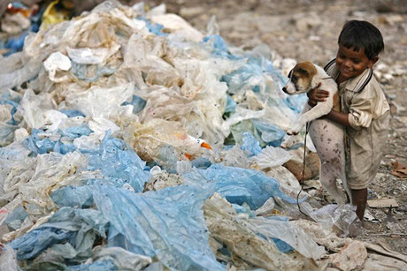 Two-year-old Manik plays with a dog at a garbage dump in Dhaka (Reuters)