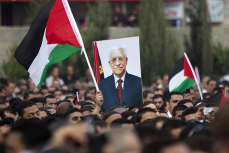 Palestinians hold national flags and a poster of Palestinian President Abbas during a celebration in Ramallah (Reuters)