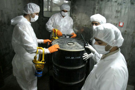 Iranian technicians lift a barrel of &quot;yellow cake&quot; to feed it into the processing line of Uranium Conversion Facility (Reuters file)