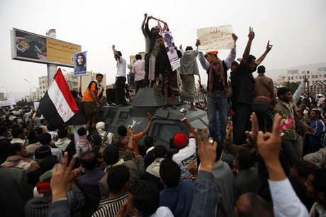Anti-government protesters stand on an armoured personnel vehicle belonging to the defected army backing them during a demonstration demanding the trial of Yemeni President Ali Abdullah Saleh in Sanaa (Reuters)