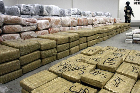 A soldier stands guard next to packages containing marijuana found in the tunnel under the Mexico-US border in Tijuana (Reuters)