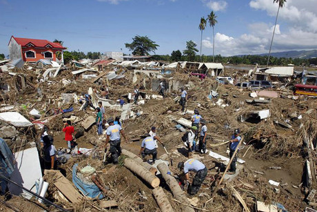 Policemen search for missing Typhoon Washi victims in a subdivision in Iligan city (Reuters)