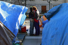 An Occupy DC couple kiss among the tents at Freedom Plaza in Washington (Reuters)