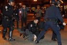 Group of police officers from various law enforcement agencies arrest Occupy Oakland demonstrator (Reuters)