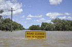 A flood warning sign starts to disappear below floodwaters near Charleville, Australia (Reuters)