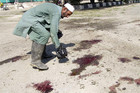 Afghan man inspects the scene of a suicide bomb attack in Khost province (Reuters)