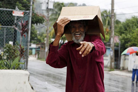 A man uses a box to protect him from the rain in Kingston (Reuters)