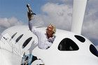Branson waves a model of the LauncherOne cargo spacecraft from a window of an actual size model of SpaceShipTwo (Reuters)