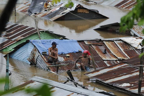 People sit on the rooftop of houses submerged in floodwaters in the neighbourhood of Barquita, after days of heavy rain in Santo Domingo (Reuters)