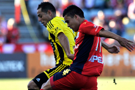 Wellington Phoenix's Leo Bertos (left) and Adelaide United's Iain Ramsay contest the ball (AAP)