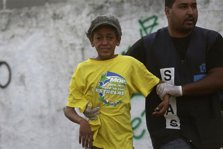 Municipal agent detains boy during operation by Rio de Janeiro's Social Action Secretariat near Parque Uniao slum (Reuters)