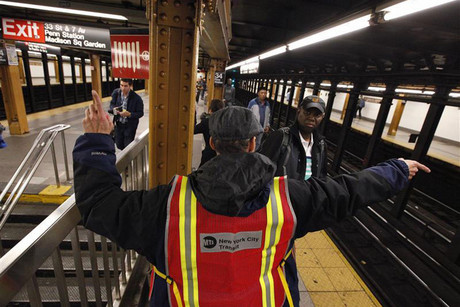 A New York City Transit worker directs people to board the last train in New York (Reuters)