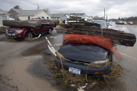 Cars sit under debris left from Hurricane Sandy in Queens borough in New York (Reuters)