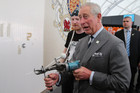 Prince Charles uses a tufting gun to work on a wool carpet in Auckland (AAP)