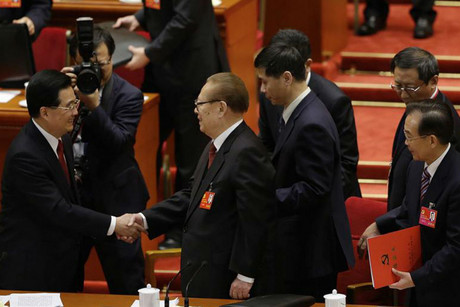 China's Hu and Jiang shake hands as Wen Jiabao holds his ballot to take a vote (Reuters)