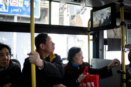 Bus passengers in Shanghai watch the Communist Party's announcement of its new leaders (Reuters)