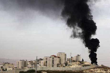 Smoke rises above a section of the Israeli barrier near Jerusalem  (Reuters)