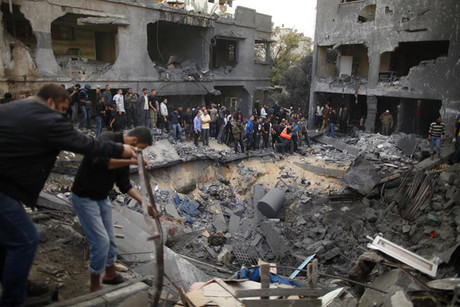 Palestinians gather around destroyed house after an Israeli air strike in Gaza City (Reuters)