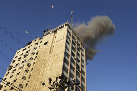 Smoke and debris are seen after Israeli air strike on office of Hamas television channel Al-Aqsa (Reuters)