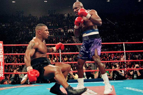 Evander Holyfield knocks down Mike Tyson in 1996 and he doesn't want the gloves he used auctioned off (Reuters file)