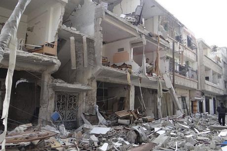 Buildings damaged after Syrian Air Force fighter jets fired missiles in Erbeen, near Damascus (Reuters)