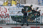 A Hamas policeman walks past a mural depicting an exploded Israeli tank, in Gaza City (Reuters/Mohammed Salem)