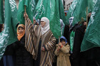 Palestinians wave Hamas flags during a rally  (Reuters)