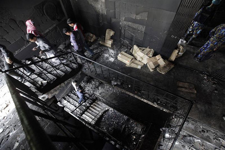 Members of the police inspect the burnt interior of a garment factory after a fire (Reuters)