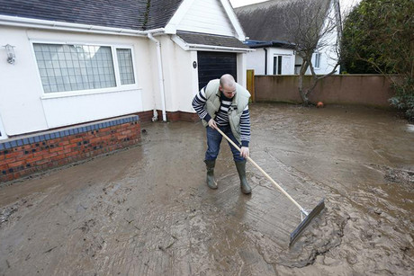 A resident in north Wales cleans up after flooding (Reuters)