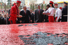 Albanian Prime Minister Sali Berisha (C-L) and Kosovo Prime Minister hashim Thaci (C-R) start to cut a huge cake with the symbols of Albanian flag and measuring 550 metres square, in the main boulevard of Tirana, Albania (AAP)