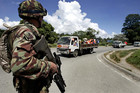 New Zealand soldier protects a convoy of Solomon Islanders in 2006 (Reuters)