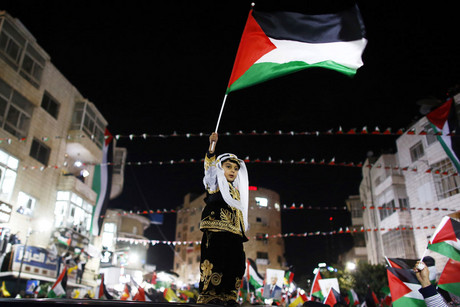 A Palestinian boy in traditional clothes waves a Palestinian flag during a rally in the West Bank city of Ramallah (Reuters/Marko Djurica)
