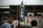 A gigantic model of a local-made M75 long range rocket is seen on stage during a preparations for Hamas rally in Gaza (Reuters)