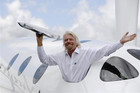 Branson waves a model of LauncherOne cargo spacecraft from a window of an actual size model of SpaceShipTwo (Reuters)