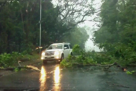 Broken branches cover a road in Nadi as the storm intensifies