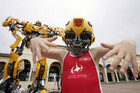 A young child poses in front of a &quot;life-size&quot; Transformer in Sydney, 2009 (AAP)