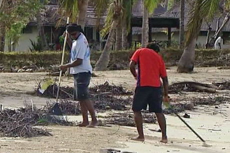 Workers clear debris scattered across the beach by Cyclone Evan
