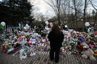 A mourner stands at a makeshift memorial in Sandy Hook village (Reuters)