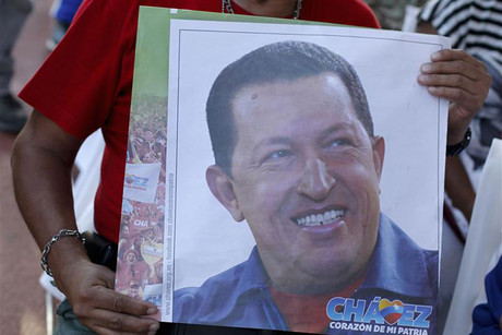 A supporter of Venezuelan President Chavez holds a picture of him, as he attends a mass to pray for Chavez's health in Caracas (Reuters)