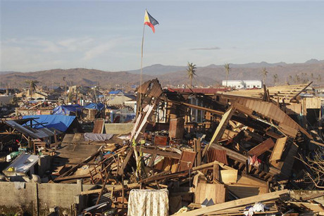 A Philippine flag flutters amidst houses destroyed in the coastal town of Cateel (Reuters)
